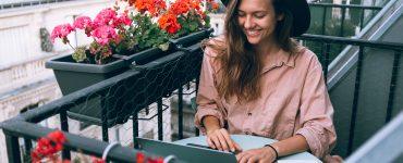 laptop ile balkonda freelance çalışan kız